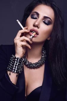 Élégante femme brune chaude fumant une cigarette sur fond noir en studio