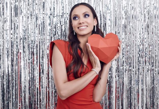 Élégante femme brune hispanique en robe rouge luxueuse détient un coeur en papier