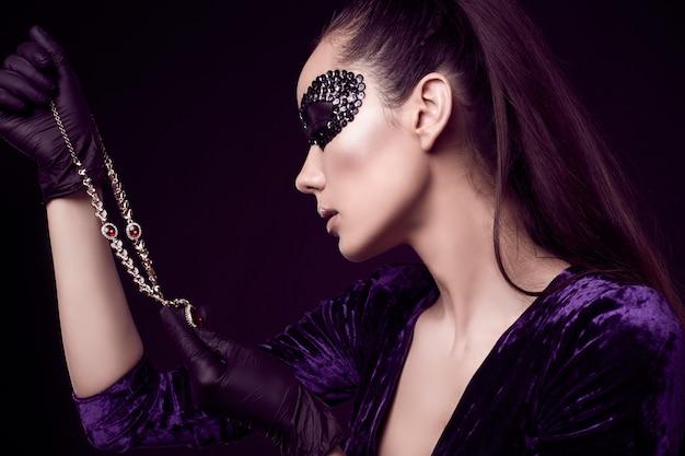Élégante femme brune en masque de paillettes avec des gants noirs se penche sur le collier de diamants