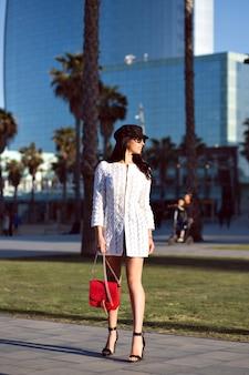 Élégante femme brune qui marche, tenue de style luxe fantaisie, bâtiments modernes et palmiers, couleurs toniques.
