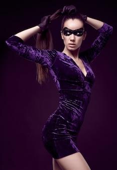 Élégante femme brune en robe violette et masque de paillettes avec des gants noirs