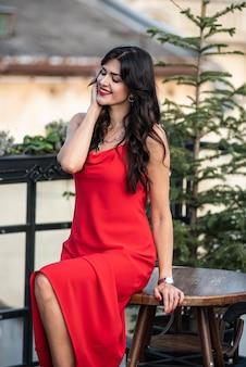 Élégante femme caucasienne avec de longs cheveux bruns raides en robe élégante rouge