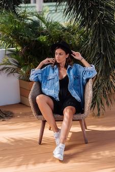 Élégante femme caucasienne en robe, chapeau et veste en jean s'asseoir sur une chaise