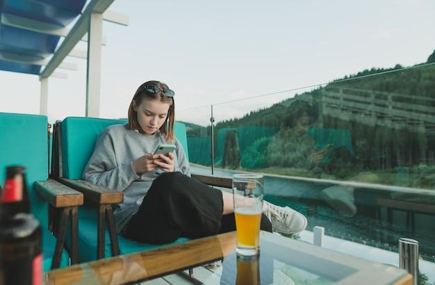 Élégante femme détendue avec smartphone, restant près de l'étang et des sapins