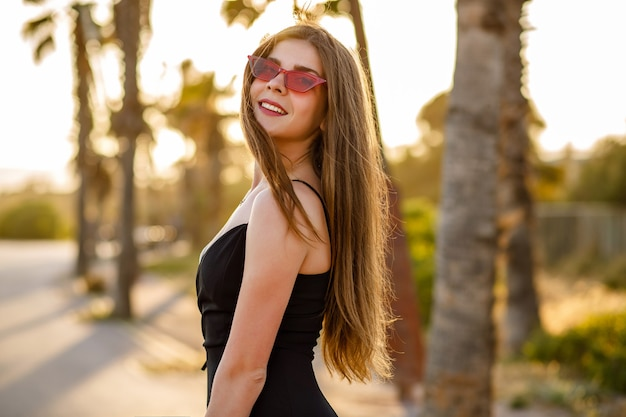 Élégante femme élégante posant près de palmiers au coucher du soleil