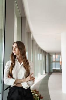 Élégante femme entrepreneur prospère regardant par la fenêtre comme couloir de bureau debout.