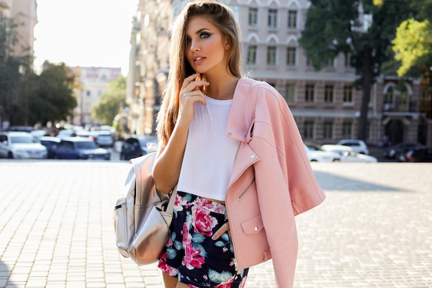 Élégante femme européenne blonde en veste de cuir rose posant en plein air.
