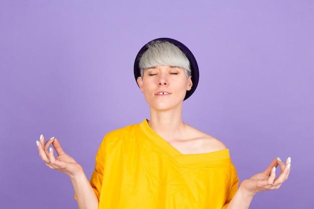 Élégante femme européenne sur mur violet. se détendre et sourire en faisant un geste de méditation avec les doigts