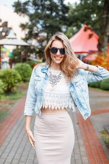 Élégante femme heureuse jeune hipster avec beau sourire dans des vêtements élégants à lunettes de soleil lors d'une promenade dans un parc d'attractions sur une journée ensoleillée d'été