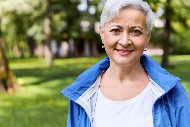 Élégante femme joyeuse à la retraite ayant une belle promenade dans la forêt ensoleillée le jour d'été avec un sourire heureux, profitant du beau temps et de l'air frais, des arbres et de l'herbe verte