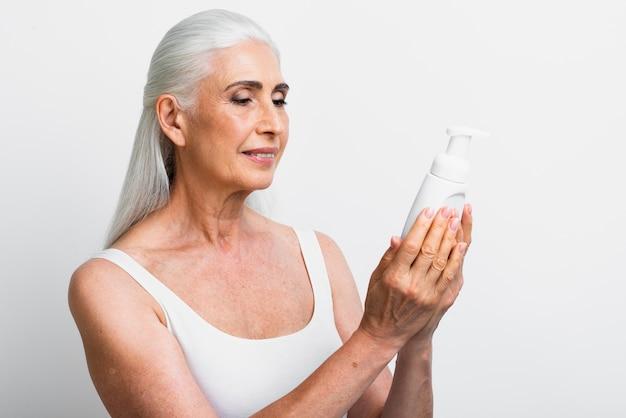 Élégante femme mûre tenant un produit de soin de la peau