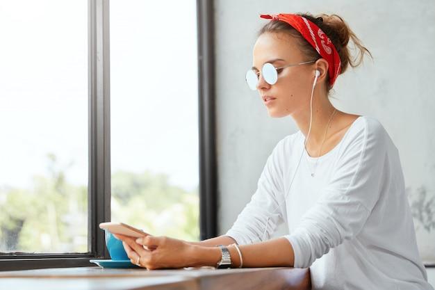Élégante femme portant un bandana assis dans un café