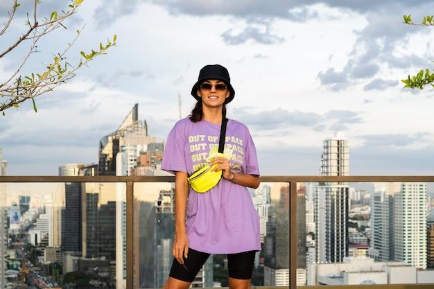 Élégante femme de race blanche en panama branché et sac néon taille sur le toit à bangkok
