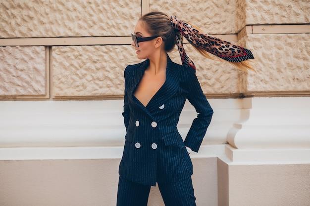 Élégante femme sexy vêtue d'un costume de smoking élégant marchant dans la ville le jour du printemps d'été