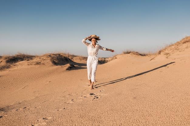 Élégante femme souriante belle qui court dans le sable du désert en tenue blanche portant un chapeau de paille sur le coucher du soleil