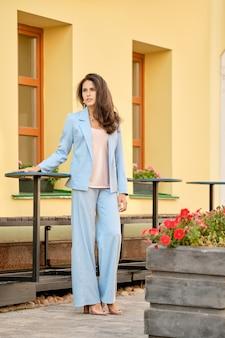 Élégante femme en tailleur pantalon bleu ciel en attente près de la table au café