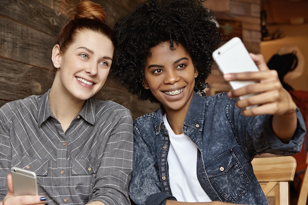 Élégante fille afro-américaine avec coupe de cheveux afro tenant mobile, prenant selfie