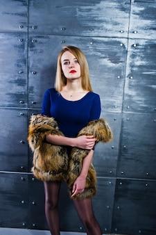 Elégante fille blonde porte un manteau et une robe combi en fourrure