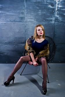 Elegante fille blonde porter sur manteau de fourrure et robe combi posée sur une chaise contre un mur en acier
