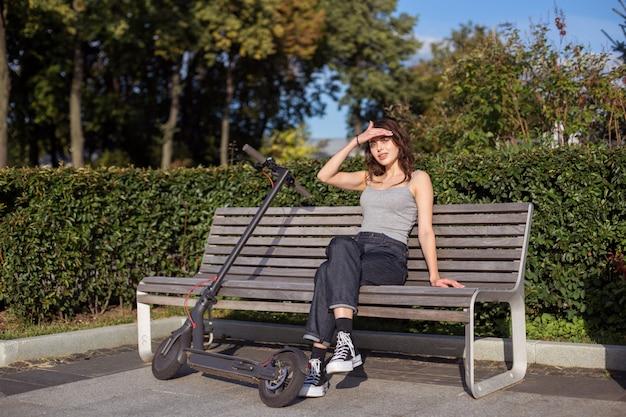 Élégante fille brune assise sur un banc avec son escooter dans un parc en plein air par temps ensoleillé