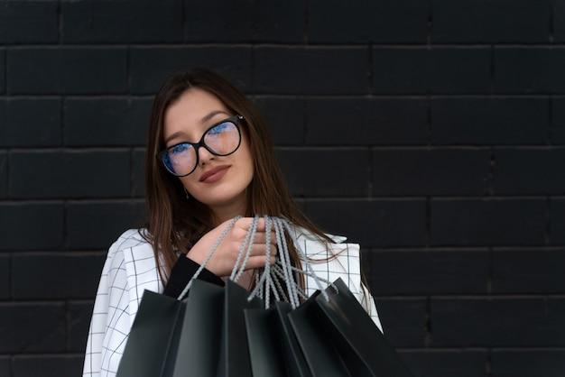 Élégante fille étudiante dans des verres détient des sacs noirs contre le mur noir