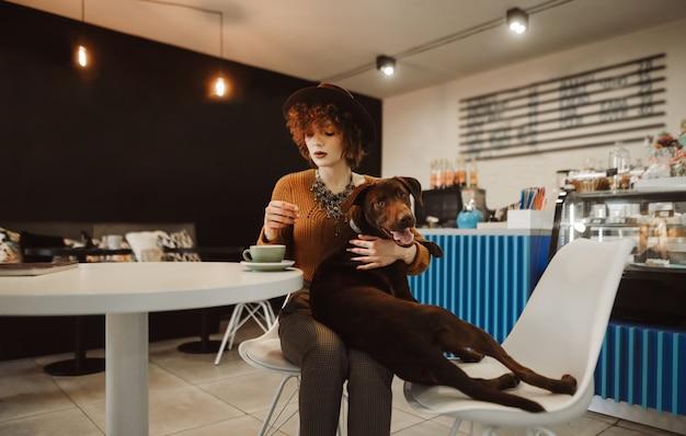 Élégante fille habillée aux cheveux bouclés se trouve dans un café avec un chien sur ses genoux et boit du café