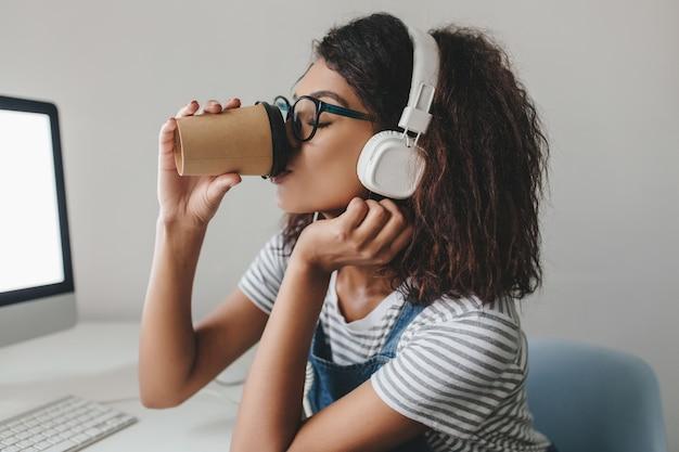 Élégante fille noire avec une coiffure frisée, boire du café sur le lieu de travail posant près de mur gris