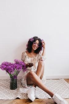 Élégante fille noire exprimant son bonheur lors d'une séance photo en intérieur avec des fleurs. portrait de femme africaine heureuse assis sur le sol avec bouquet et téléphone.