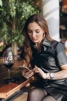 Élégante et glamour belle femme en robe de latex noir avec smartphone au restaurant.