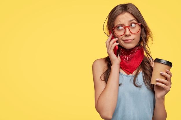 Élégante jeune brune avec des lunettes posant contre le mur jaune