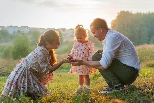 Élégante jeune famille de maman, papa et fille blonde d'un an assis près du père sur les épaules, à l'extérieur de la ville dans un parc