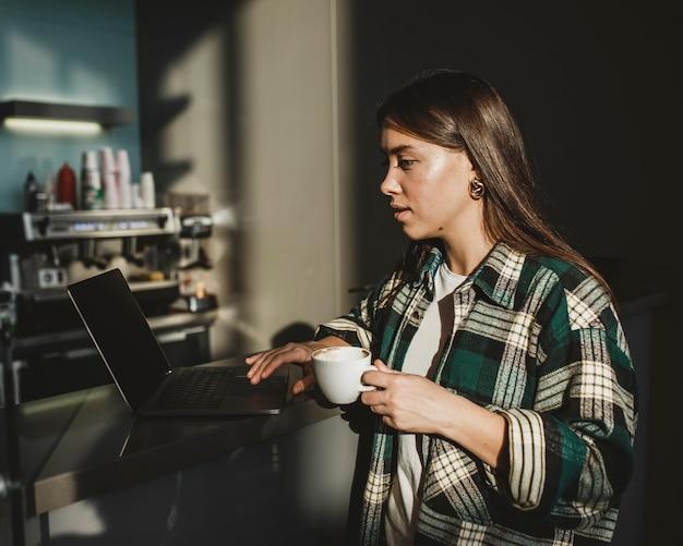 Élégante jeune femme appréciant le café