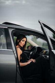 Élégante jeune femme assise dans une voiture de classe affaires dans une robe noire