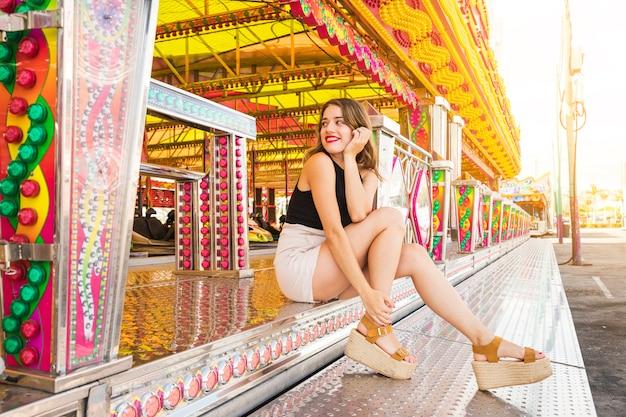 Élégante jeune femme assise près du manège forain