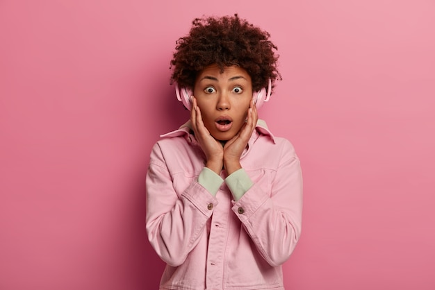 Élégante jeune femme aux cheveux bouclés garde les mains sur les joues, porte une veste rose, écoute la radio en ligne, utilise des écouteurs sans fil, a choqué l'expression du visage