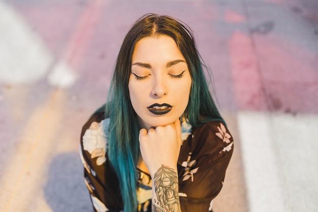 Élégante jeune femme aux lèvres noires et aux cheveux teints fermant les yeux
