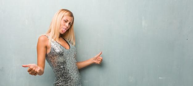 Élégante jeune femme blonde excitée célébrant un événement dansant.