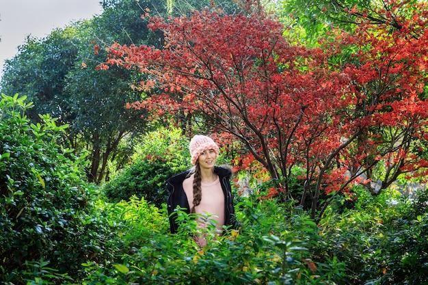 Élégante jeune femme en bonnet rose debout dans le parc