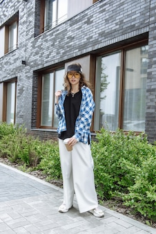 Élégante jeune femme brune à lunettes et beaux vêtements à la mode posant sur le fond d'un catalogue de rue de la ville.
