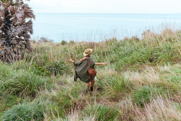 Élégante jeune femme en chemise kaki marchant dans les steppes, voyageant en afrique en safari, portant chapeau et sac à dos marron, explorant la nature, temps ensoleillé. style boho. vue arrière