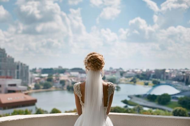 Élégante jeune femme avec une coiffure élégante, en robe de mariée en dentelle et voile de mariée regarde la vue de la ville, préparation du mariage de la jeune mariée