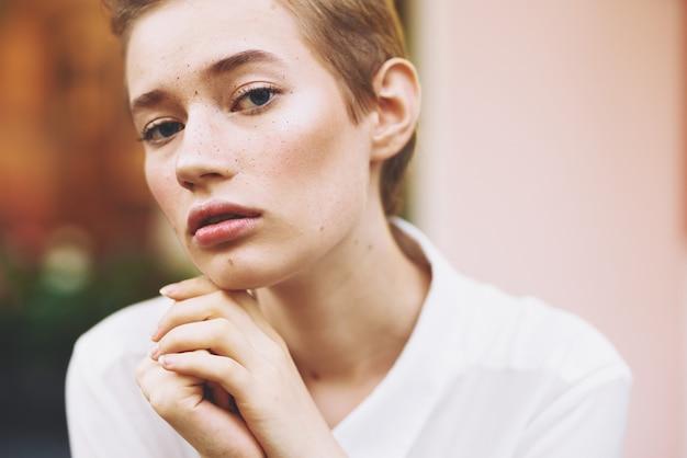 Élégante jeune femme dans une chemise avec un livre dans ses mains est assise à une table dans un café en été