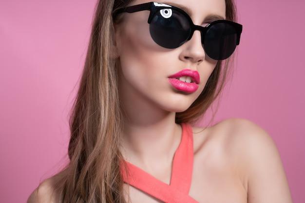 Élégante jeune femme dans un joli costume rose et des lunettes de soleil posant sur rose