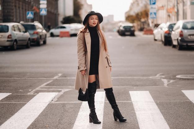 Élégante jeune femme dans un manteau beige dans un chapeau noir dans une rue de la ville. mode de rue pour femmes. vêtements d'automne style urbain.