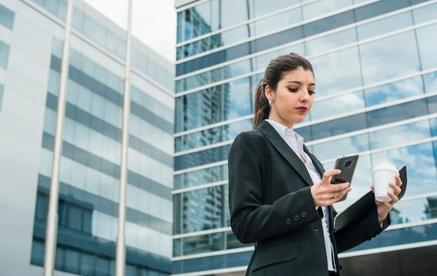 Élégante jeune femme debout devant le message de texto de bâtiment d'entreprise sur téléphone mobile