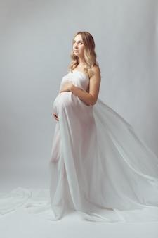Élégante jeune femme enceinte debout portant un tissu blanc volant grossesse maternité et maternité