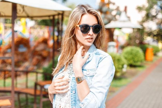 Élégante jeune femme hipster à la mode dans des lunettes de soleil en veste en jean d'été bleu à la mode en chemisier en dentelle blanche vintage sur une promenade dans un parc d'attractions