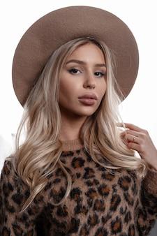 Élégante jeune femme incroyable dans un chapeau beige luxueux avec des lèvres sexy aux yeux bruns aux cheveux blonds bouclés dans un pull léopard