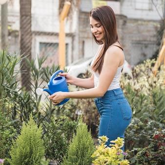Élégante jeune femme en jeans arroser la plante