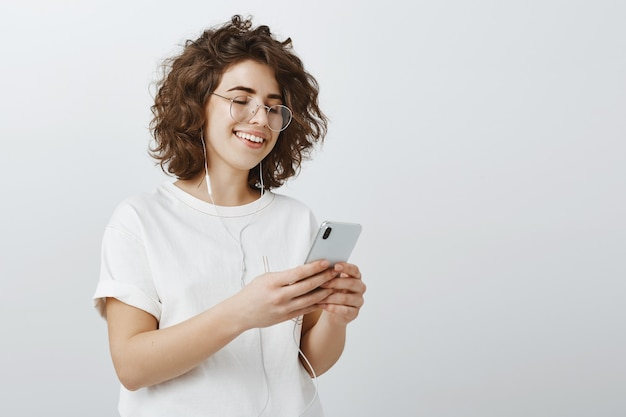 Élégante jeune femme à lunettes faisant une liste de lecture dans le téléphone, écouter de la musique via des écouteurs